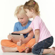 Two cute children sitting on the floor and playing with touchpad