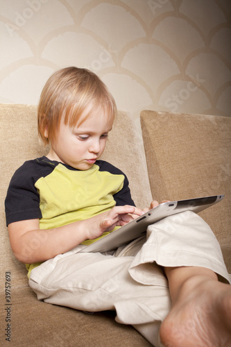 positive small boy with tablet computer
