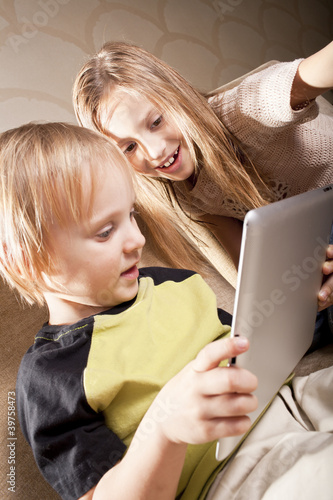smiling girl and boy with tablet computer