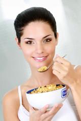 Jeune femme mangeant des céréales au petit déjeuner