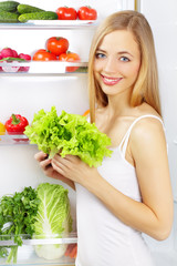 girl with a green salad. Background of the refrigerator