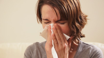 Sneezing woman having a cold.