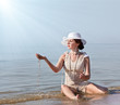 Woman in white hat posing against the sea