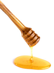 honey flowing down from a wooden honey dipper