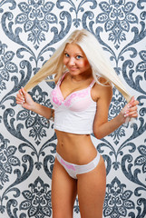 Young beautiful sexy blonde woman in white lingerie on vintage w