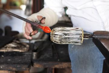 Glass blower shaping molten glass