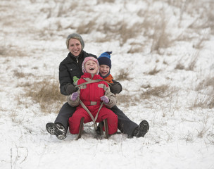 Happy family slides with sledge on snowy hill
