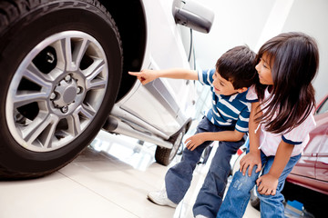Kids looking at car wheels