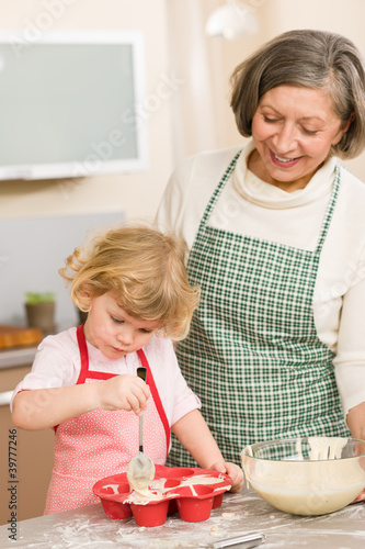 Woman and little girl baking cupcakes together