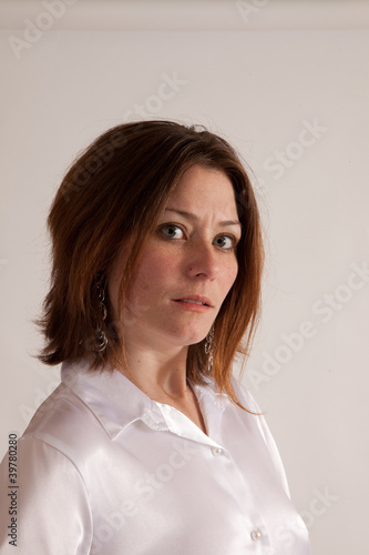 Woman wearing white silk shirt, looking at camera