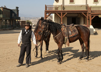 Sheriff holding two horses at Mini Hollywood