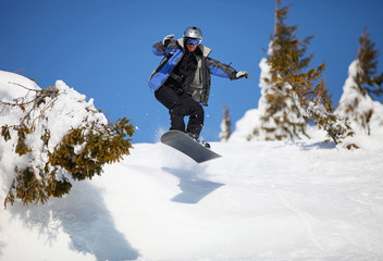Snowboarder jumping on mountain slope