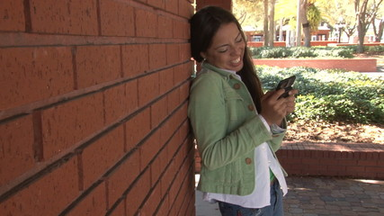 Happy student sending funny text message on campus