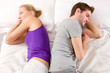couple lying in bed back-to-back having lovers' quarrel