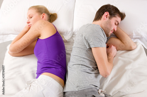 couple lying in bed back-to-back