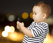 portrait of funny kid touching mobile at city by night
