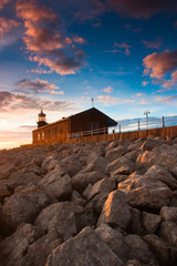 Lighthouse on the pier - Scenic view of rocky sea defences