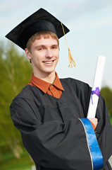 graduate student in gown with diploma