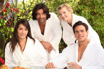Two couples in their bathrobe in the garden.