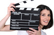 Young woman with a film clapperboard