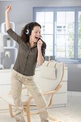 Happy woman singing with headphones