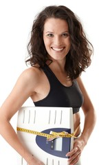 Laughing sporty woman with scale
