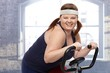 Happy woman on exercise bike