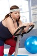 Exhausted fat woman on exercise bike