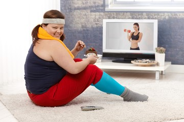 Overweight woman eating chocolate cake smiling