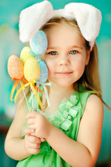 sweet little girl dressed in Easter bunny ears holding colorfull