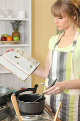 Woman preparing a meal with the help of a recipe