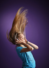 Girl with headphones on purple background