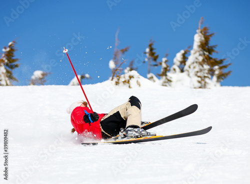 Girl skier falling down white on mountain slope