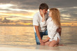 Young couple on the sea sunset background