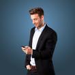 junger attraktiver Mann mit Mobiltelefon