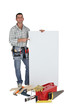 Carpenter stood with blank advertising panel