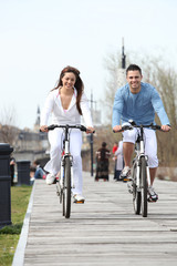 Young couple riding bikes along a boardwalk