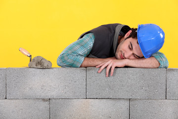 Builder asleep on a wall