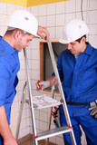 Two electricians watching plan