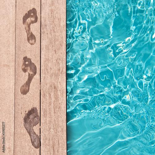 Leinwanddruck Bild Traces de pieds nus au bord d'une piscine