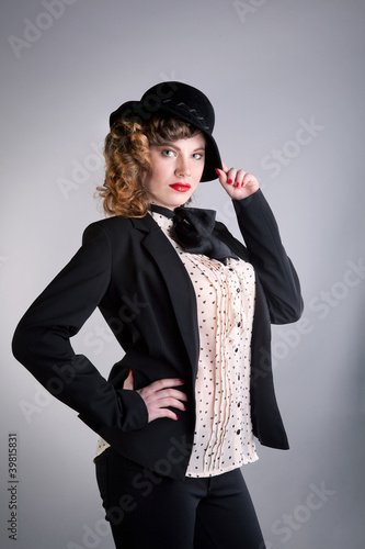 The girl in a black suit and in a hat poses in studio