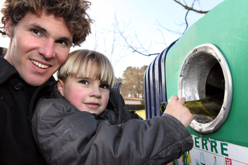 Father and son recycling glass bottles