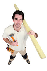 Handyman holding a hammer and carrying a wooden plank
