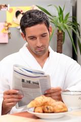 man having breakfast with newspaper