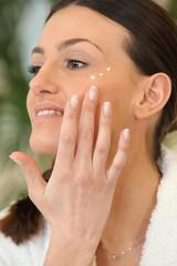 Brunette applying moisturiser