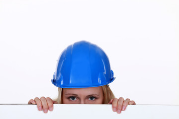 Tradeswoman peering over a low wall