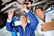 Mechanics working under a car