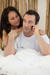 Couple making telephone call whilst in bed