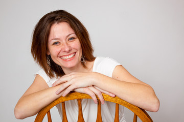 woman sitting backwards in a chair and smiling
