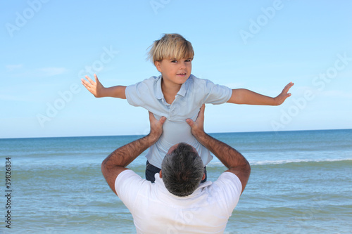 A father carrying his son by the beach.